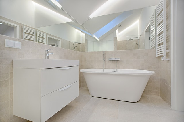 ensuite with vanity and bathrub and skylight